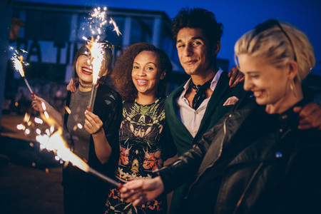 Friends at night with fireworks enjoying party