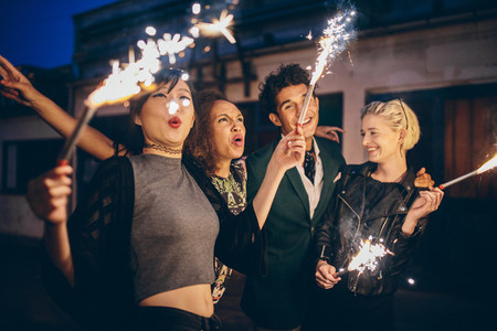 Young people enjoying new years eve with fireworks