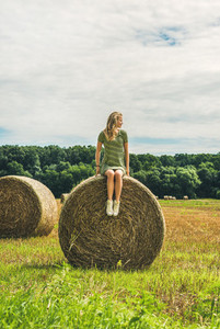 Young blond lady sitting on haystack and looking away  Hungary