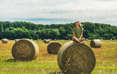 Young blond lady sitting on haystack and smiling  Hungary