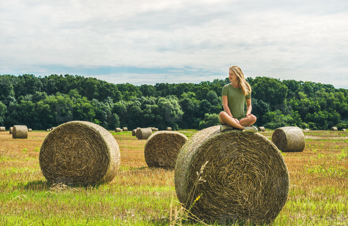Young blond girl sitting on haystack and smiling  Hungary