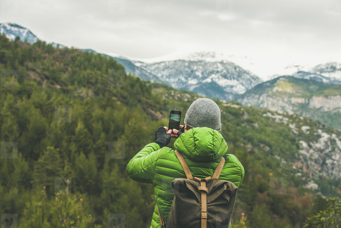 Young man traveller making photo of mountains and green slopes