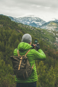 Young man traveller making photo of green valley and slopes