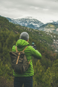 Young man traveller wearing bright clothes making photo of landscape