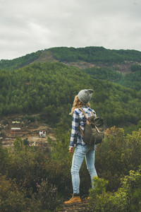Young woman traveler hiking in the mountains  rear view
