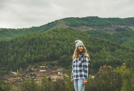 Young woman traveler in chekered shirt hiking in the mountains