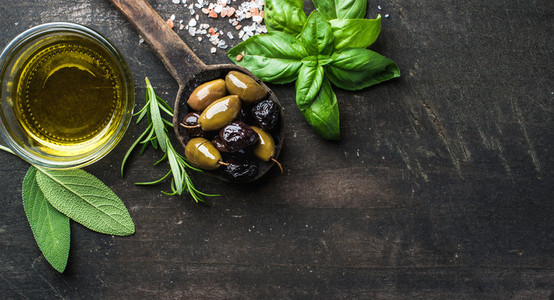 Green and black Mediterranean olives in old cooking spoon