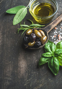 Green and black Mediterranean olives with fresh herbs