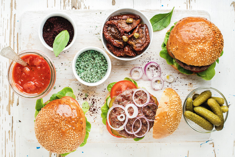 Homemade beef burgers with onion  pickles  vegetables  sun dried tomatoes  sauce