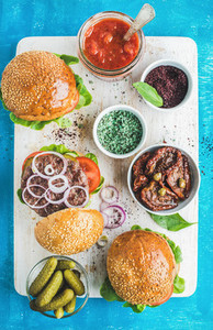 Homemade beef burgers with onion pickles vegetables and sun dried tomatoes