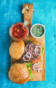 Homemade beef burgers with onion fresh vegetables spices tomato sauce