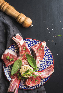 Raw uncooked lamb chops with herbs and spices on colorful plate over dark wooden background