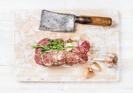 Raw roastbeef meat cut with rosemary  thyme and garlic
