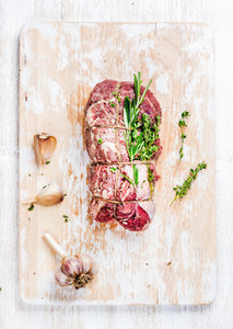 Raw roastbeef meat cut with rosemary thyme and garlic vertical