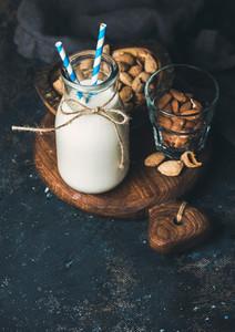Fresh almond milk in bottle with almonds over dark background