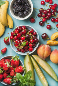 Healthy summer fruit variety on blue wooden backdrop