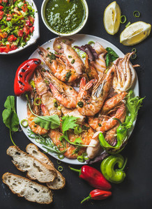Plate of roasted tiger prawns and octopus pieces with fresh leek  salad  peppers  lemon  bread  pesto sauce over black background