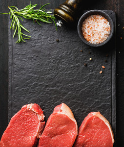Raw beef Eye Round steaks with spices  rosemary  Copy space