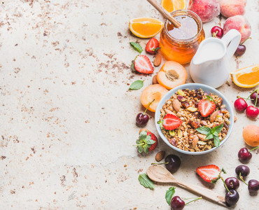 Healthy breakfast ingredients  Oat granola in bowl with nuts  strawberry and mint leaves  milk in pitcher  honey in glass jar  fresh fruits  berries on light concrete background  copy space