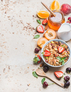 Healthy breakfast ingredients Oat granola in bowl with nuts strawberry and mint leaves pitcher honey in jar fresh fruits berries on light concrete background copy space