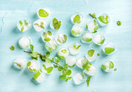 Ice cubes with frozen mint leaves inside on blue Turquoise background top view
