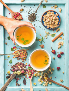 Two cups of healthy herbal tea with mint cinnamon dried rose camomile flowers in spoons and man039s hand holding spoon