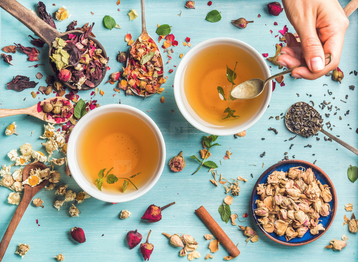 Two cups of healthy herbal tea with mint  cinnamon  dried rose  camomile flowers in spoons and man s hand holding spoon