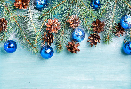 New Year or Christmas background fir branches  blue glass balls and pine cones over turquoise wooden backdrop  copy space