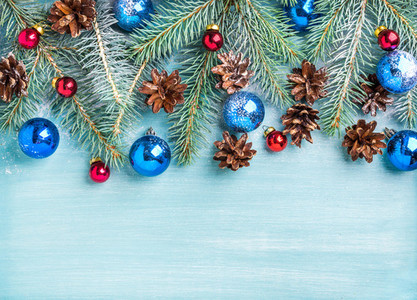 New Year or Christmas background fir branches colorful glass balls cones over blue painted wooden backdrop copy space