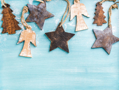 New Year or Christmas background wooden angels  stars and small fir trees over blue painted backdrop  copy space