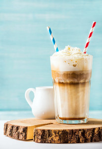 Latte macchiato with whipped cream in tall glass   two straws and pitcher on wooden board over blue painted wall background  copy space