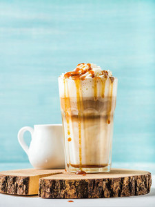 Latte macchiato with whipped cream and caramel sauce in tall glass on round wooden serving board over blue painted wall background