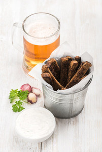 Beer snack set  Pint of pilsener in mug and rye bread croutons with garlic cream cheese sauce  fresh parsley over white painted old wooden background