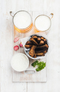 Beer snack set  Two mugs of pilsener  rye bread croutons  garlic cream cheese sauce and fresh herb over white painted old wooden backgroundwith