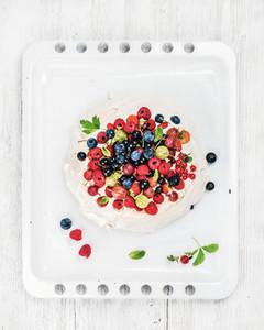 Homemade Pavlova cake with fresh garden berries on white baking tray over light wooden background