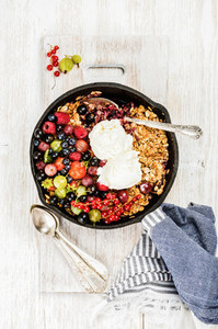 Oat granola crumble with berries and ice cream over white backdrop
