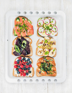 Sweet and savory breakfast toasts assortment  Sandwiches with fruit  vegetables  eggs  smoked salmon on white baking tray over light wooden background