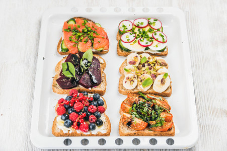 Sweet and savory breakfast toasts variety Sandwiches with fruit vegetables eggs smoked salmon on white baking tray over light wooden background