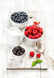 Fresh berries and milk in pitcher on white wooden background