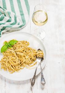 Pasta spaghetti with pesto sauce  basil  glass of white wine