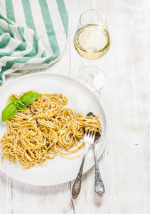 Pasta spaghetti with pesto sauce basil glass of white wine