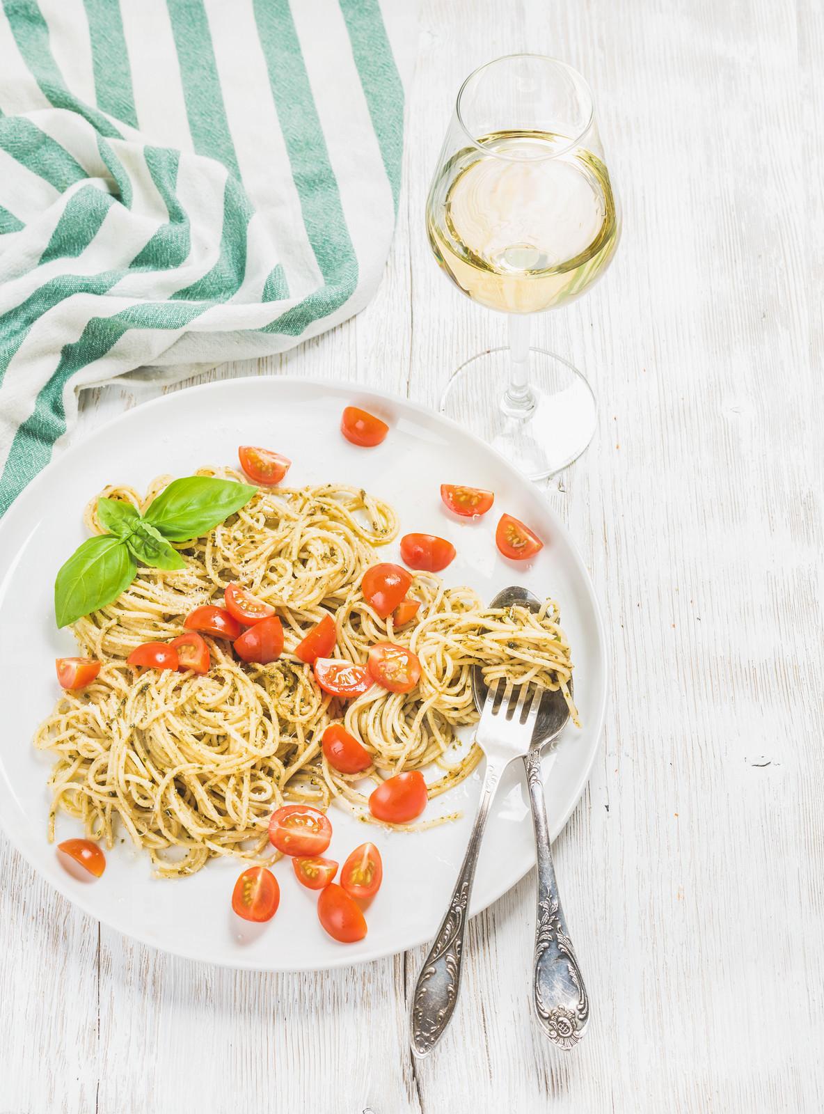 Pasta spaghetti with pesto sauce  cherry tomatoes  white wine