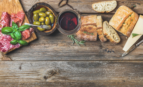 Wine snack set and glass of red over wooden background