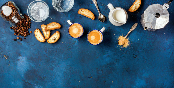 Coffee espresso cantucci cookies and milk over dark blue background