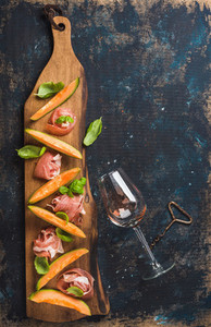 Prosciutto  cantaloupe melon and wine glass over dark plywood background