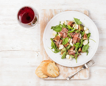 Prosciutto arugula figs salad with baguette slices and wine
