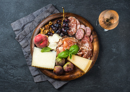 Italian antipasti snack for wine on wooden tray  dark background