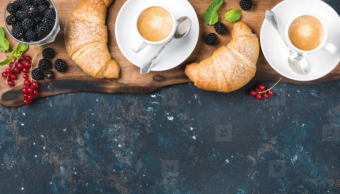 Freshly baked croissants with garden berries and coffee cups