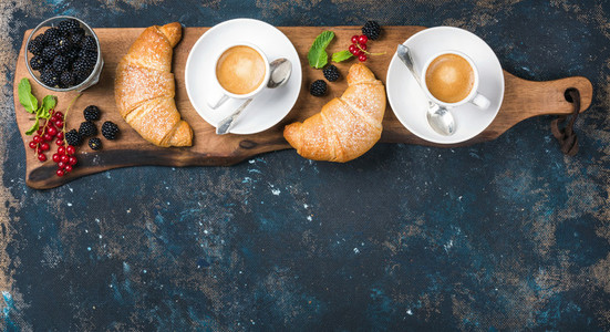 Freshly baked croissants with garden berries and espresso