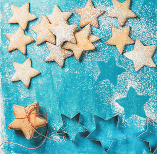 Christmas gingerbread cookies sprinkled with sugar powder on blue background